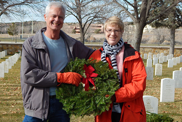 LANL employees holding holiday wreaths at cemetery