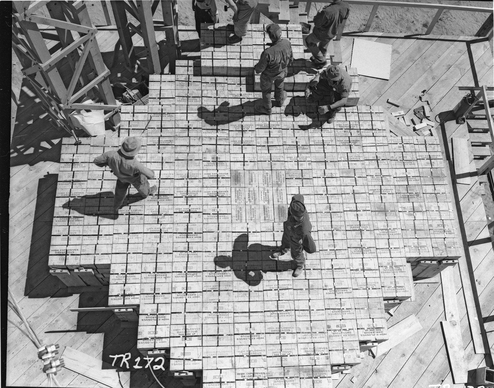 Workers stand on top of stacks of TNT.