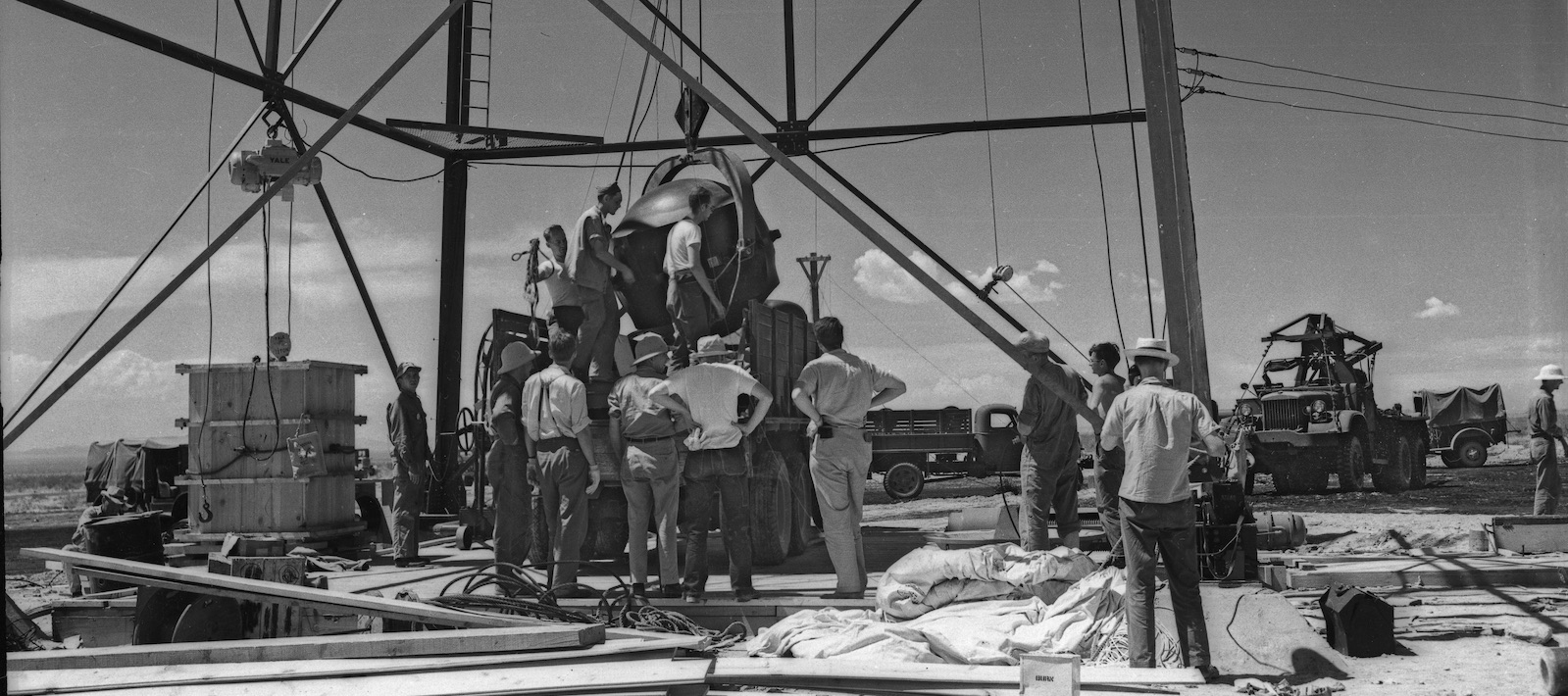 A group of men surrounding the Gadget, which is about to be lifted out of a truckbed and up into the tower.