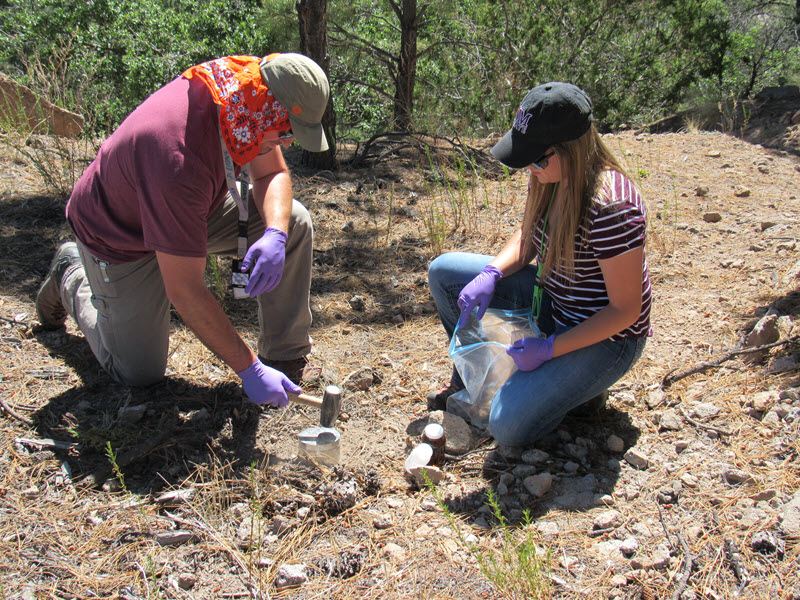 Two Laboratory environmental field team members take soil samples from a perimeter location.