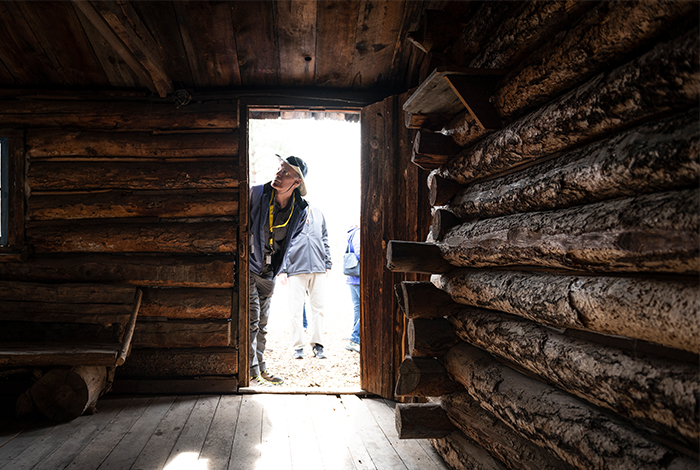 A visitor peers inside Pond Cabin.