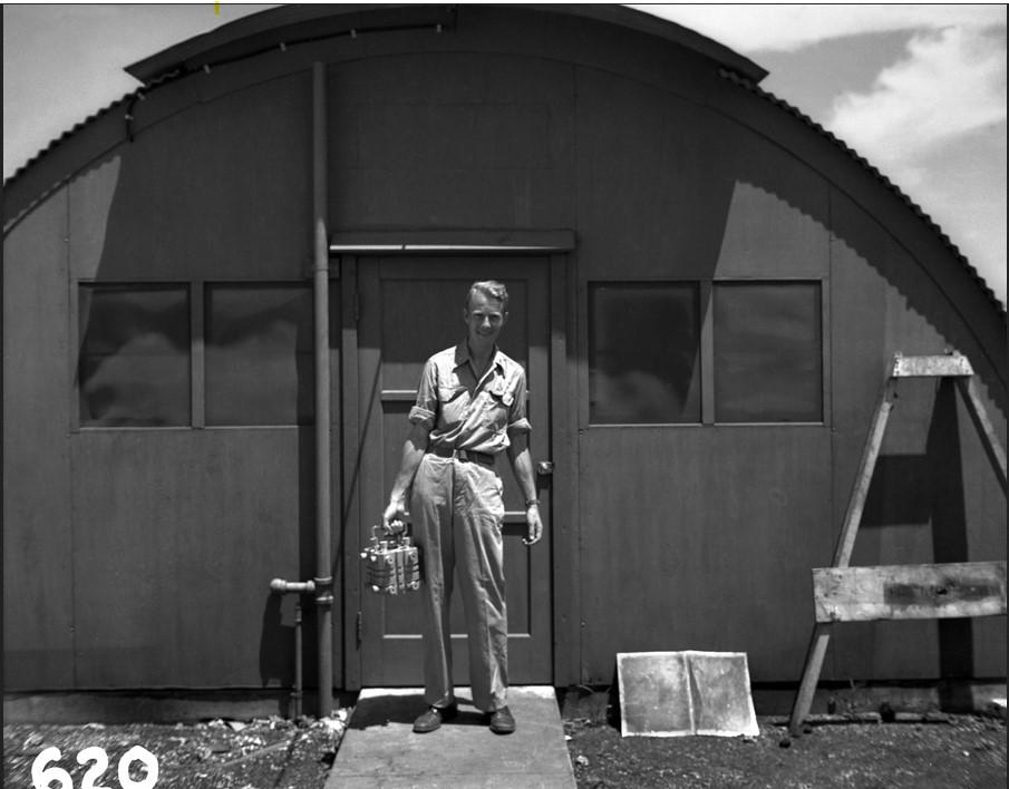 Physicist Luis Alvarez holding Fat Man's plutonium core carrier on Tinian island.