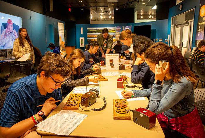 Here, a group of students work on Manhattan Project activities at the Museum — pre-pandemic (so no masks or social distancing).