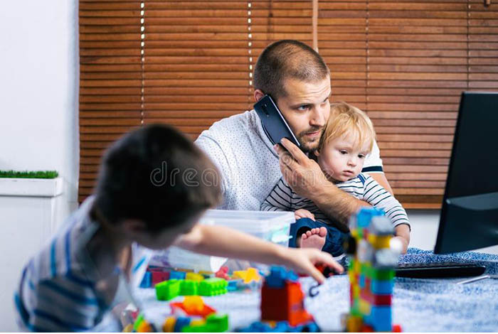 Image of parent working from home with children.