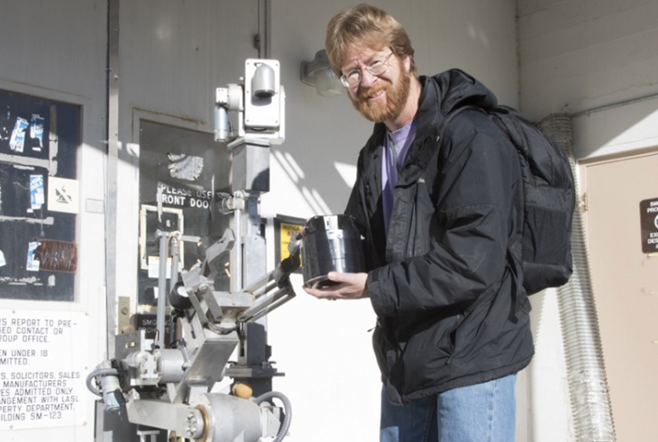 scientist pictured with Gamma Lightthouse Detector on a robot